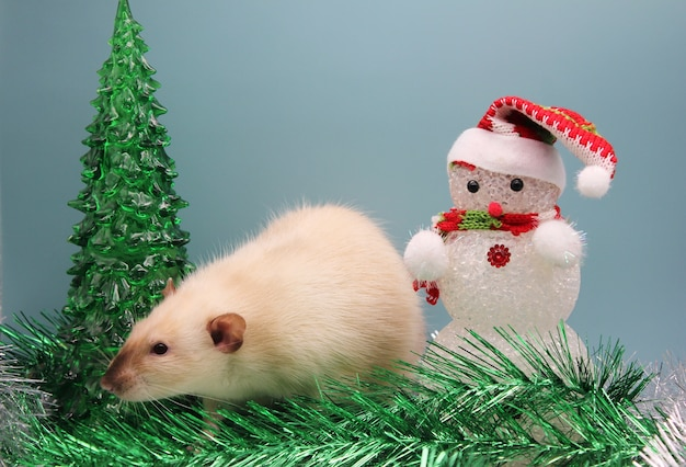 おもちゃのクリスマスツリーの近くのネズミと見掛け倒しの雪だるま。