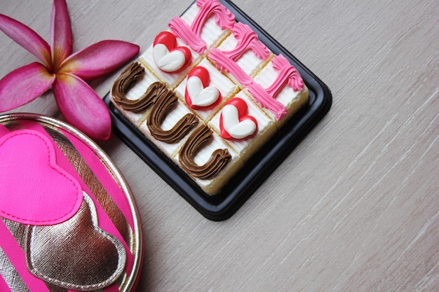 Торты с надписью «я тебя люблю», цветочек и косметическая сумка с сердечками на нем.