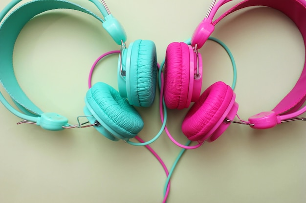 ピンクとターコイズ色のヘッドフォンの部品が近くにあります。