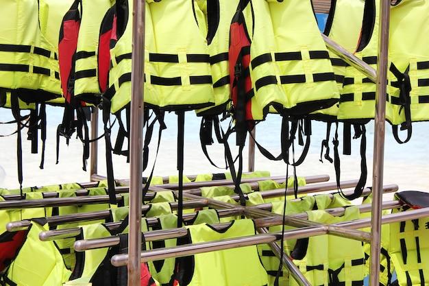 Много ярких желтых спасательных жилетов висит