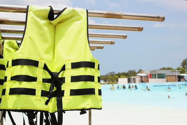 Ярко-желтый спасательный жилет висит рядом с бассейном в аквапарке