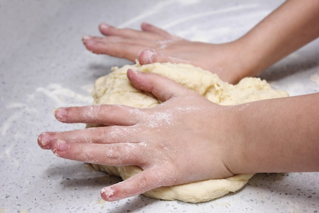 Детские руки замешивают кусок теста.