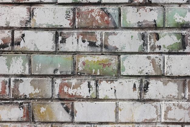 使い古されたパターンと古い塗料の痕跡でレンガの壁