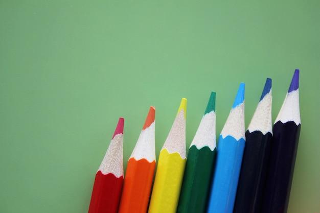 色鉛筆虹色は緑の背景に一列に配置されます。