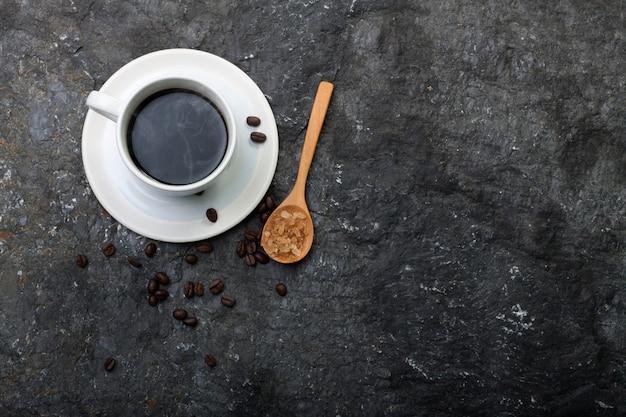 白いカップコーヒー、黒い石の上の木のスプーンで砂糖