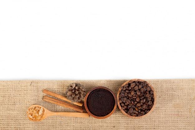 木製のカップのコーヒー豆、黄麻布の松の木のスプーンで砂糖