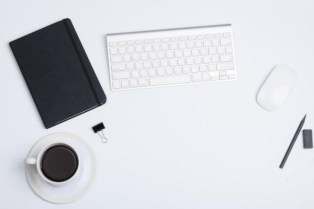 フラット横たわっていた、トップビューの近代的なオフィスのテーブルデスク。ブラックブックコーヒー、マウス、ブラックペン、キーボード