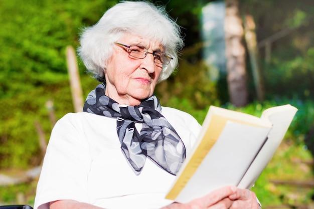 Крупным планом пожилая женщина читает роман