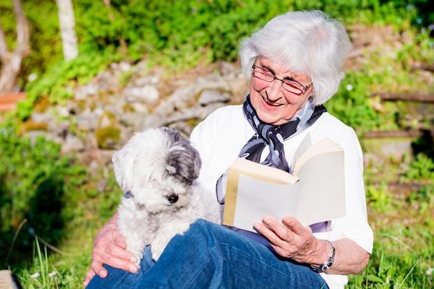 Счастливая женщина читает со своей собакой