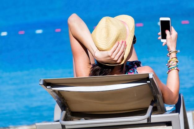 彼女の携帯を見つめて横たわっている女性