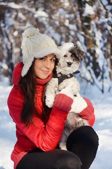 Улыбается девушка позирует со своей собакой в снежном поле