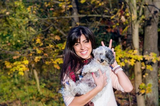 Веселая женщина, держащая ее собаку на открытом воздухе