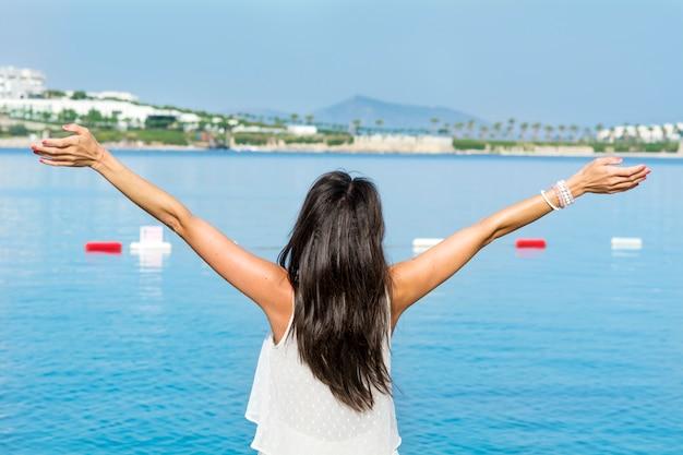 ビーチで開いた腕を持つ女性