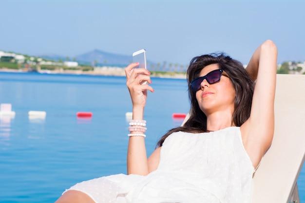 女は、彼女の携帯を見て