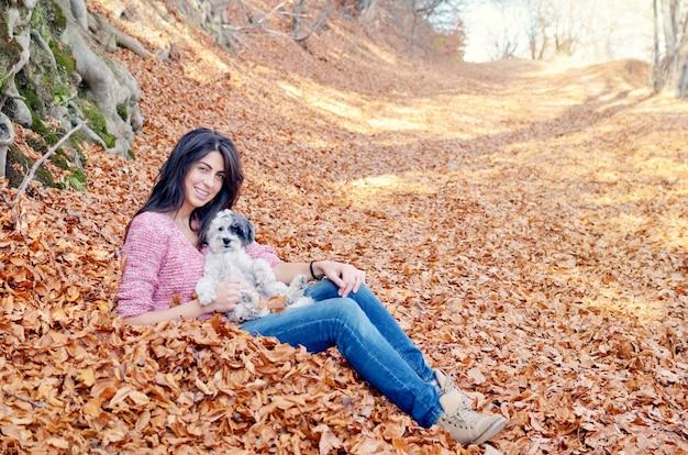 Счастливая женщина со своей собакой на осенний день