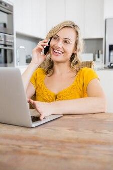 Улыбаясь женщина разговаривает по телефону ее