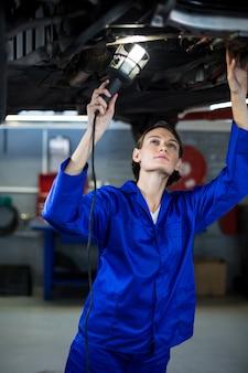 Женщина механик осматривает автомобиль с лампой