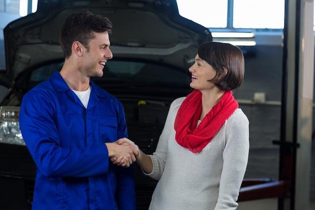Удовлетворенный клиент рукопожатие с механиком