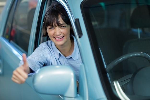 Клиент показывает палец вверх во время вождения автомобиля
