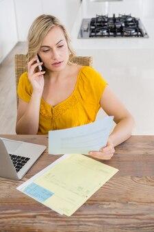 Женщина разговаривает по ее телефону во время работы