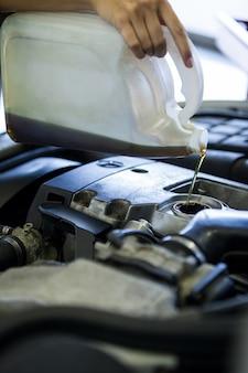 メカニックは、車のエンジンにオイル潤滑剤を注入します