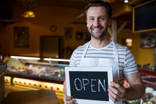 ベーカリーショップで開いて看板を保持している笑顔の所有者