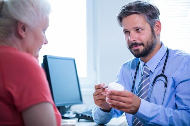 医師は、診療所で患者に薬の瓶を支援します