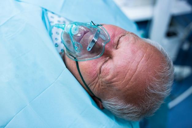 手術室で酸素マスクでベッドに横たわっている患者