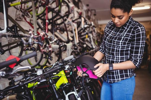 自転車用ヘルメットを調べるメカニック