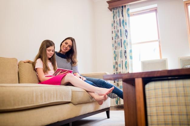 Мать и дочь, используя цифровой планшет в гостиной