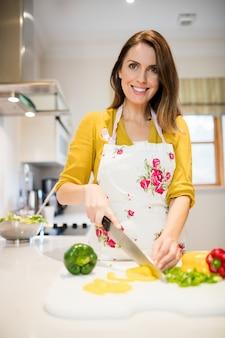 女はまな板に野菜をカット