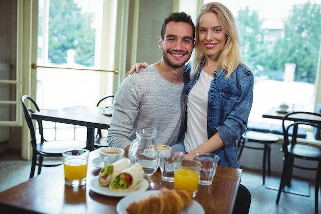 腕周りに座って笑顔のカップルの肖像画