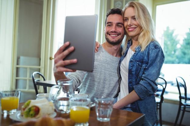 デジタルタブレットからカップル取って写真を笑顔