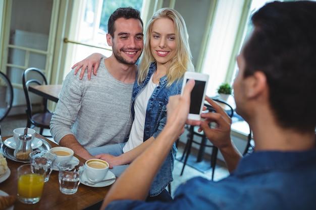 携帯電話からのカップルの写真をクリックすると友達
