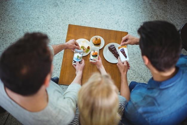 Друзья щелкая фотографий сладкой пищи