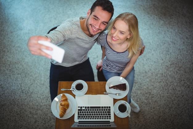 Молодая пара, принимая селфи в кафе