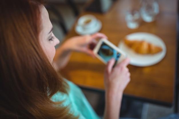 携帯電話からクロワッサンの写真をクリックする女