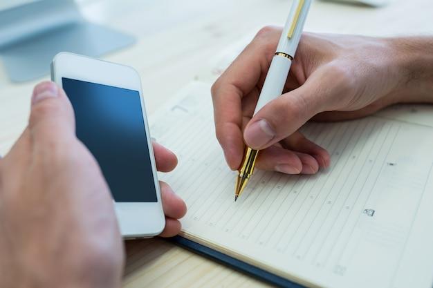 男性のグラフィックデザイナーの手日記に書いたり、携帯電話を保持しています