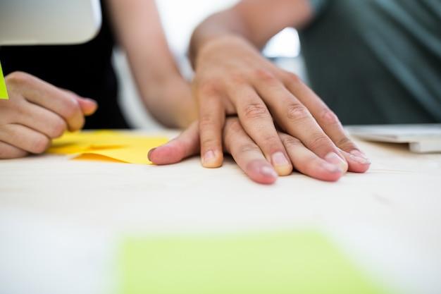 机の上のカップルの手のクローズアップ