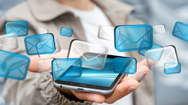 ビジネスマンの携帯電話で電子メールを送信する