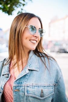 完璧な白い歯が付いている通りでスタイリッシュな笑顔幸せな若い女性の肖像画を間近します。夏のファッショントレンド、デニムジャケット、ブルーアイキャットサングラス、陽気、ポジティブ。ライフスタイルコンセプト。