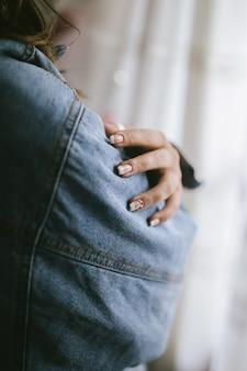 エレガントで長持ちする女性のフレンチマニキュアとカラフルなビーズとデニムジャケット。女性の手とフランスのマニキュア。美容女性の爪。女性らしさと美しさのコンセプト