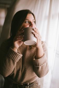 コーヒーや紅茶の瞬間を楽しんでいるファッション女性。女の子の手でコーヒーカップ。ホットドリンクのカップを持つ女性。冬の飲み物のカップ。リラックスしたコンセプト。