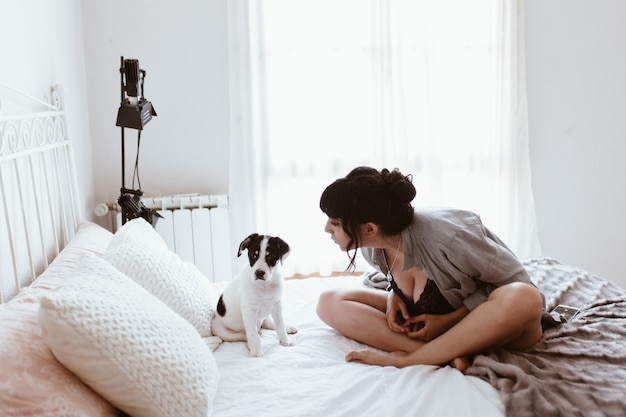 Брюнетка с милым щенком в спальне