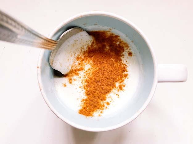 免疫システムを高めるためにマグカップにシナモンを入れたケフィア。免疫学および胃の利点は、病気や体重減少を防ぎます。健康的なベジタリアン料理。