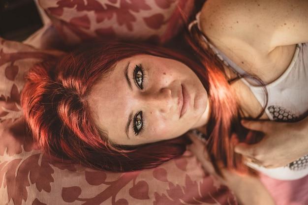 深刻なソファに横たわっている美しい緑色の目でかなり若い赤毛の女性