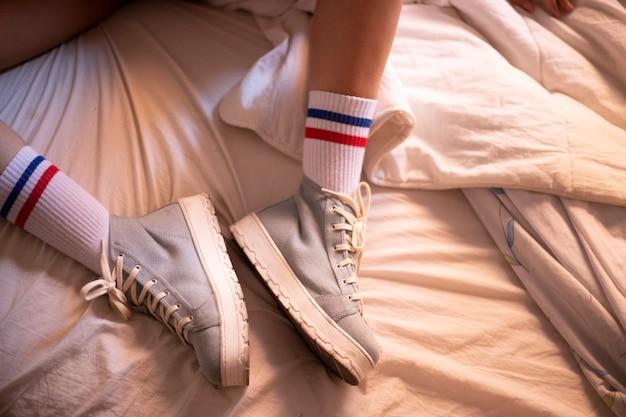 スポーツソックスが付いているベッドの上の明るい青のプラットフォームとスポーツシューズ