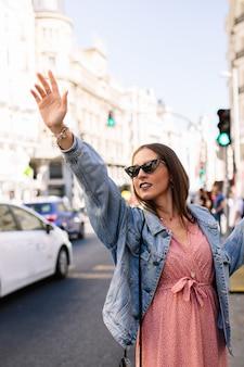マドリード市内で腕を上げるタクシーを求める若いブルネットの女性。ピンクのドレス、デニムジャケット、ブーツ、アイキャットサングラスを身に着けているファッションモデル。タクシーを呼ぶ女性。交通 。