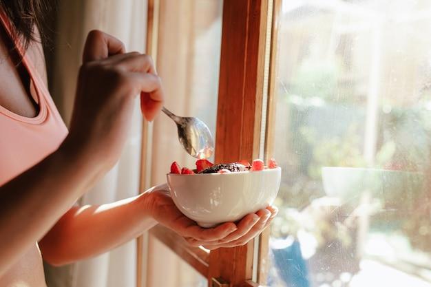 フルーツヨーグルトの種とチョコレートの朝食ボウルを食べるスポーツブラジャーを持つ若い女性