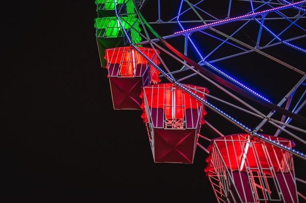 夜の観覧車のクローズアップ。夜の照明で暗い空を背景に観覧車の一部。お祭りのコンセプト。